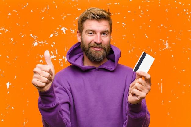 Молодой блондин человек с кредитной картой, носить фиолетовый балахон против поврежденной оранжевой стены