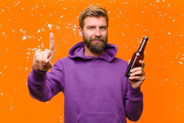 Молодой блондин человек, имеющий пиво, носить фиолетовый балахон против поврежденной оранжевой стены