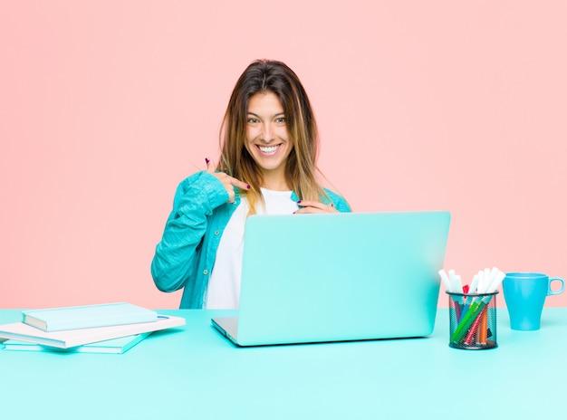 幸せ、誇りに思って、驚いて、元気に自己を指し、自信と高尚を感じているラップトップで働く若いきれいな女性