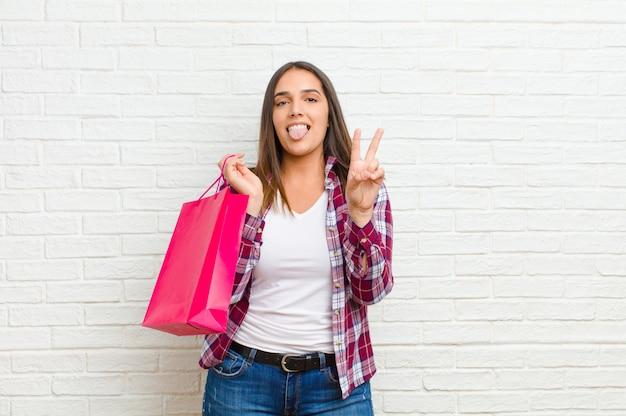 レンガの壁のテクスチャに対して買い物袋を持つ若いきれいな女性