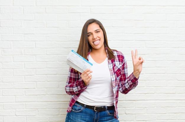 Молодая милая женщина с билетами посадочного талона против текстуры кирпичной стены