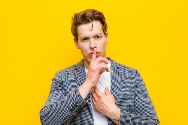 オレンジ色の壁に対して秘密を保ち、沈黙または静かを要求する唇に押された指で真剣な十字架を探している若い赤い頭の男