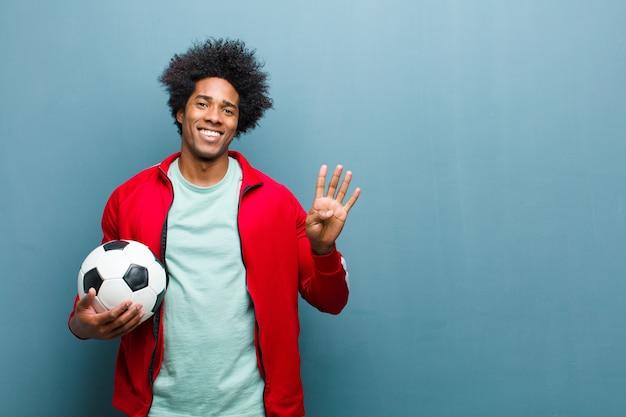 青いグランジワシントンに対してサッカーボールを持つ若い黒スポーツ男