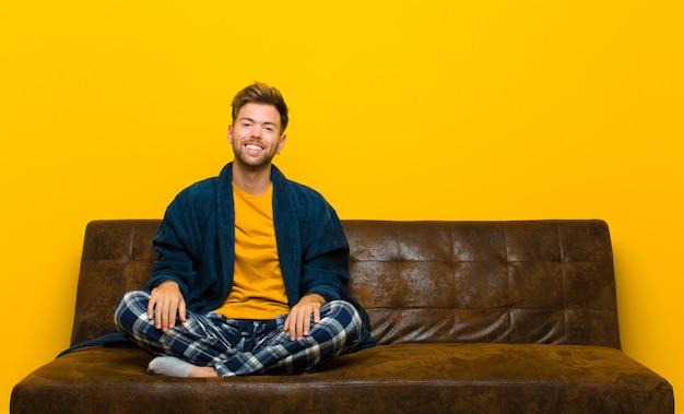 Молодой человек в пижаме с широкой, дружелюбной, беззаботной улыбкой, выглядит позитивно, расслабленно и счастливо, пугающе. сидя на диване