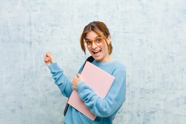 喜びと驚きを感じて、ショックを受けた表情で笑顔と側の背景を指している若い学生女性