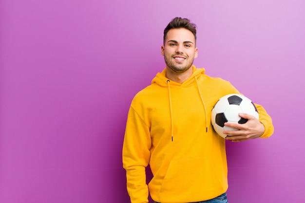 Молодой испанец человек с футбольным мячом на фиолетовом фоне