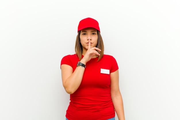 真剣に見て、沈黙または静かを要求する唇に押された指でクロスを探している配達の女性、白い背景に対して秘密を守る