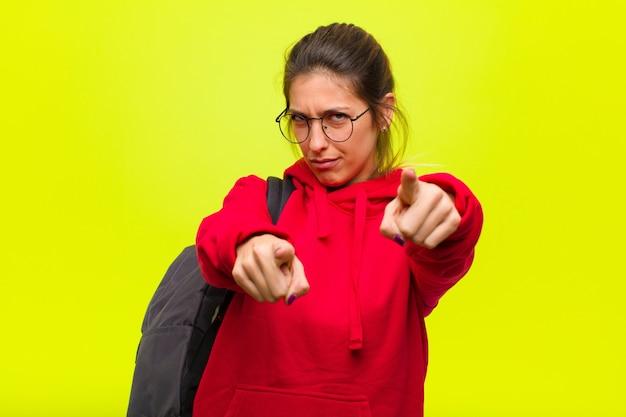 Молодой симпатичный студент, указывая пальцем на камеру двумя пальцами и выражением злости
