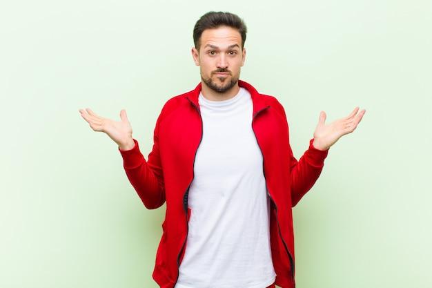 若いハンサムなスポーツ男またはモニターの感覚は困惑し、混乱、疑い、重み、またはフラット壁に対して面白い表現でさまざまなオプションを選択