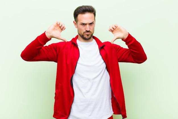 若いハンサムなスポーツ男または悲しい、失望または怒っているモニター、意見の相違で親指を示す、平らな壁に不満を感じて