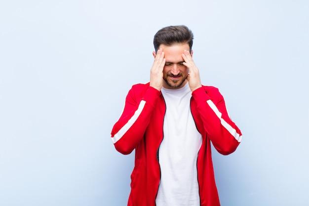 若いハンサムなスポーツ男またはストレスとイライラを探してモニター、頭痛で圧力の下で働いて、平らな壁に問題を抱えて