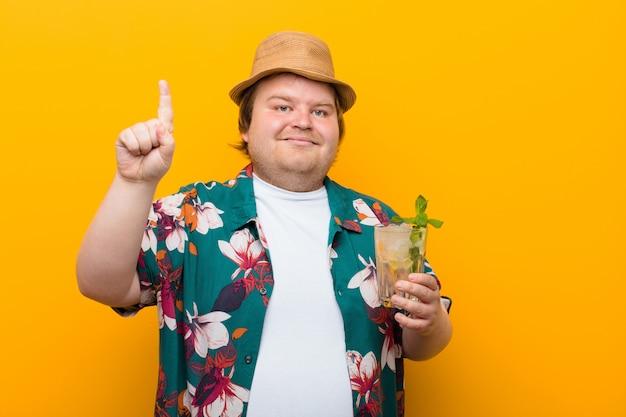 Молодой мужчина большого размера с напитком мохито на плоской стене