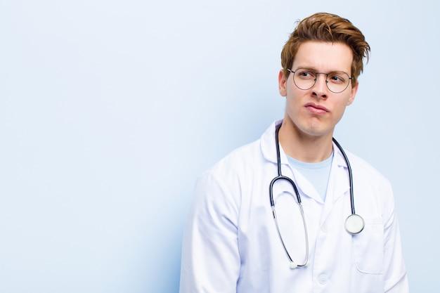 Молодой рыжий врач, чувствующий себя грустным, расстроенным или злым, смотрит в сторону с негативным отношением, хмурясь от несогласия с синей стеной