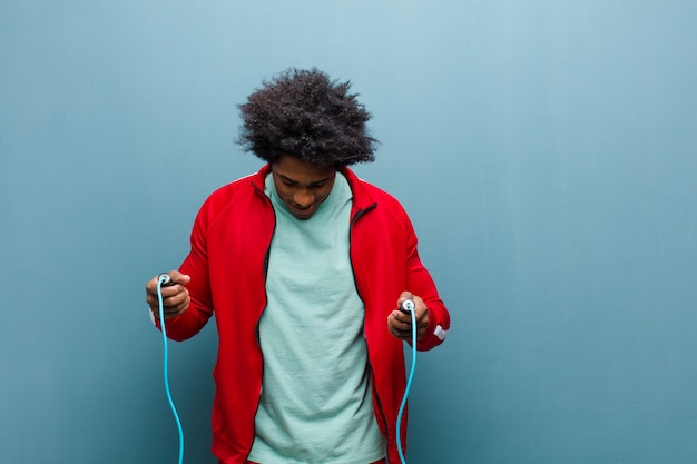 青いグランジ壁に対して若い黒人男性