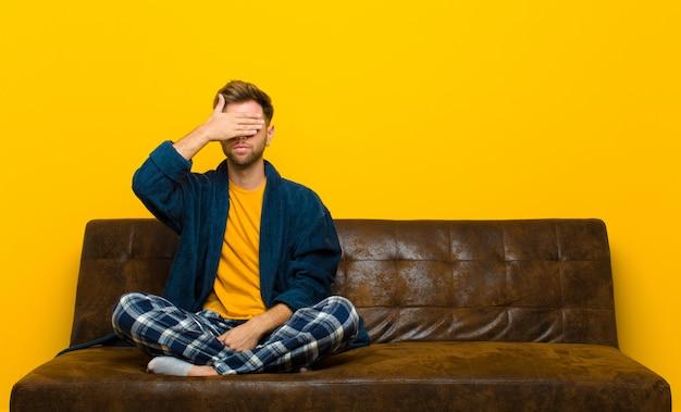 Молодой человек в пижаме, закрывающей глаза одной рукой, чувствует себя напуганным или взволнованным, удивляясь или вслепую ожидая сюрприза. сидя на диване