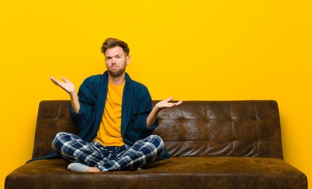 Молодой человек в пижаме выглядит озадаченным, растерянным и напряженным, размышляя о разных вариантах, чувствуя себя неуверенно. сидя на диване