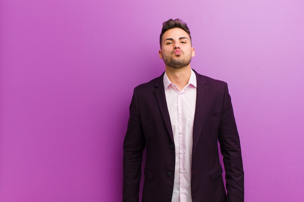 Молодой латиноамериканский мужчина, прижимающийся губами с милым, веселым, счастливым, милым выражением лица, отправляющий поцелуй