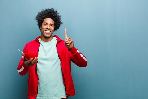 青いグランジ壁に朝食ボウルで若い黒人男性