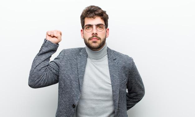 Молодой менеджер человек чувствует себя серьезным, сильным и мятежным, поднимая кулак, протестуя или борясь за революцию против белой стены