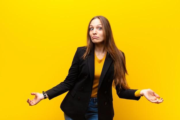Молодая симпатичная деловая женщина, чувствуя себя невежественной и растерянной, не подозревая, абсолютно озадачена тупым или глупым взглядом на оранжевом фоне