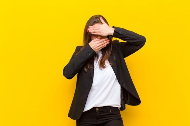 カメラにノーと言って両手で顔を覆っている若いきれいな女性!オレンジ色の壁に対して写真を拒否したり、写真を禁止したりする