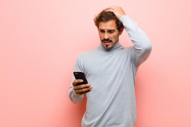 Молодой красивый человек с умным телефоном против розовой плоской стены