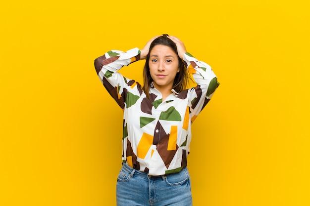 ラテンアメリカの女性はイライラし、イライラし、病気に苦しみ、失敗に疲れ、退屈で退屈な退屈なタスクに黄色の壁から隔離