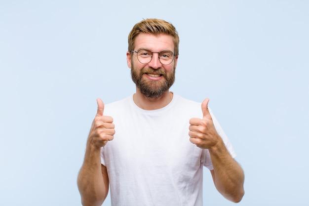 両方の親指で、広く幸せ、肯定的、自信を持って、成功を見て笑っている若い金髪の成人男性