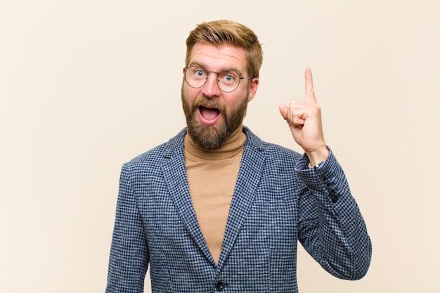 アイデアを実現し、元気よく指を上げた後、幸せで興奮した天才のように感じる若い金髪のビジネスマン、エウレカ!