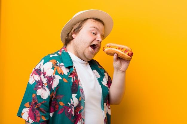 Молодой человек большого размера с хот-догом против плоской стены