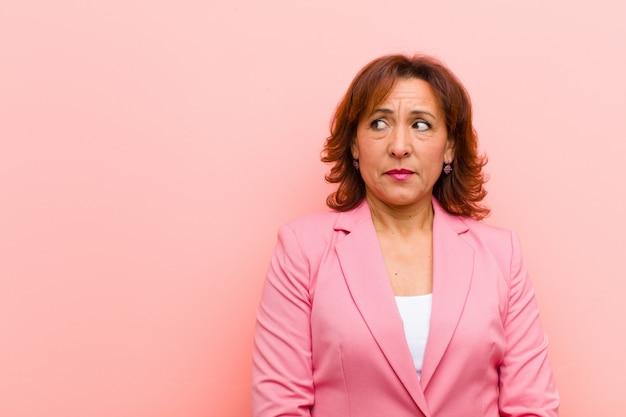 Женщина среднего возраста выглядит обеспокоенной, напряженной, взволнованной и напуганной, паникуя и стискивая зубы на розовой стене
