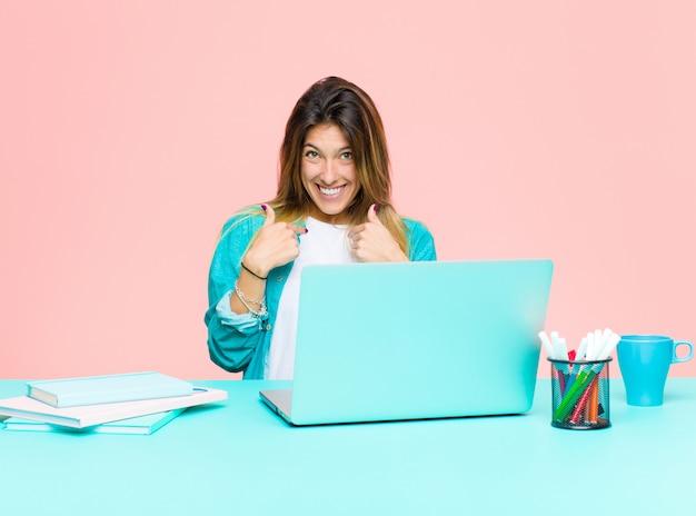 幸せ、驚き、誇りに思って、興奮して、驚いた表情で自己を指しているラップトップで働く若いきれいな女性