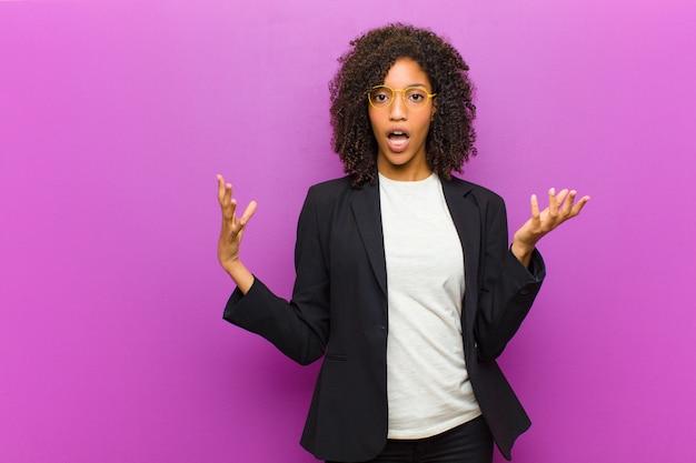 Молодая чернокожая деловая женщина, чувствуя себя чрезвычайно потрясенной и удивленной, взволнованной и панической, с подчеркнутым и испуганным взглядом