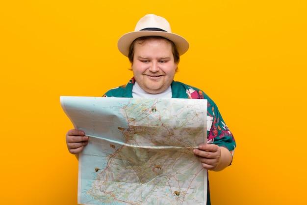 Молодой человек большого размера с картой на фоне плоской стены