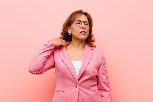 ストレス、不安、疲れとイライラ、シャツの首を引っ張って、ピンクの壁の問題にイライラして見える中年女性
