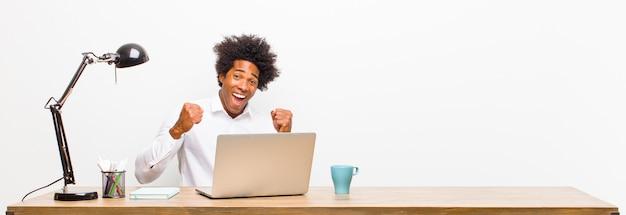 Молодой черный бизнесмен чувствует себя шокирован, взволнован и счастлив, смеясь и празднуя успех