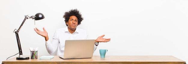 Молодой темнокожий бизнесмен, выглядящий озадаченным, растерянным и напряженным, размышляя о разных вариантах, чувствуя себя неуверенно на столе