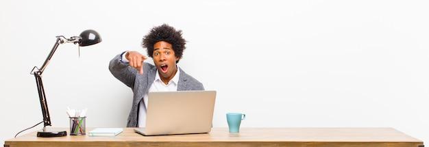 机の上の猛烈な、狂った上司のように見える怒っている積極的な表現でカメラを指して若い黒ビジネスマン