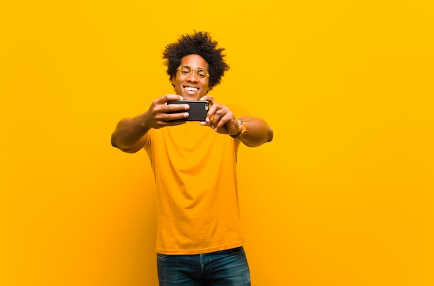 Молодой человек афроамериканца с умным телефоном на апельсине