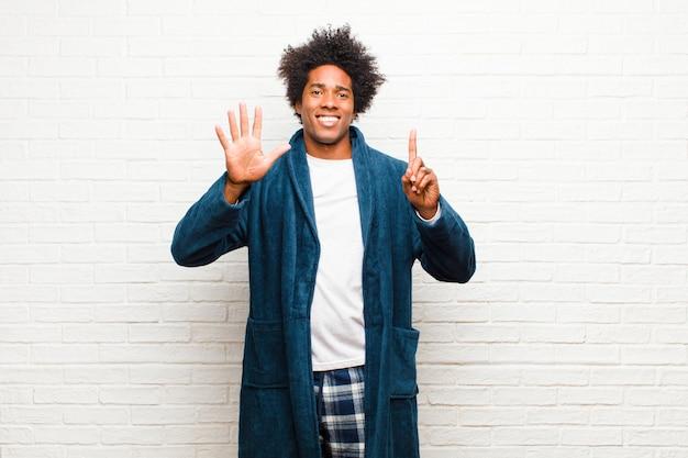 笑顔とフレンドリーな探しているガウンとパジャマを着ている若い黒人男性