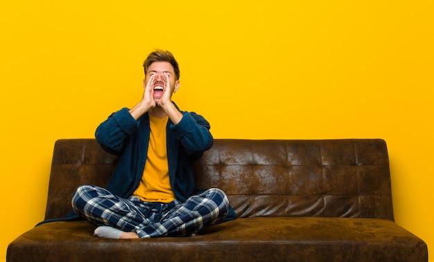 幸せ、興奮、肯定的な感じのパジャマを着た若い男、口の横にある手で大きな叫びを与える