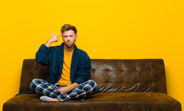 Молодой человек в пижаме чувствует себя смущенным и озадаченным, показывая, что вы ненормальный, сумасшедший или сошли с ума