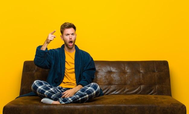 激怒のように見える怒っている積極的な表情でカメラを指してパジャマを着ている若い男