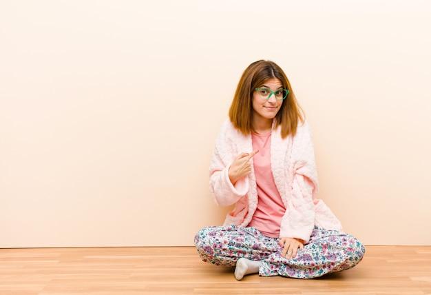 Молодая женщина в пижаме сидит дома, смотрит гордый, уверенный и счастливый, улыбается и указывает на себя или делает знак номер один