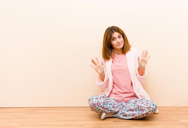 Молодая женщина в пижаме сидит дома, глядя нервной, взволнован и обеспокоен