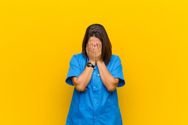 Чувство грусти, разочарования, нервозности и депрессии, закрытие лица обеими руками, плач, изолированный на желтой стене