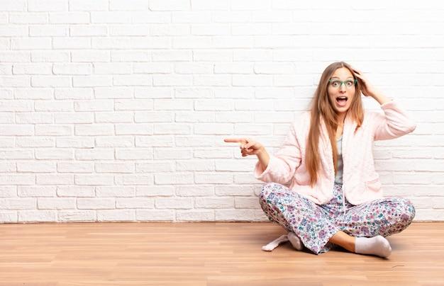 若いきれいな女性笑って、幸せな、肯定的な驚きを見て、横方向のコピースペースを指している素晴らしいアイデアを実現