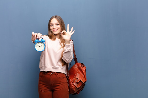 Молодая милая женщина с будильником на голубой стене с космосом экземпляра