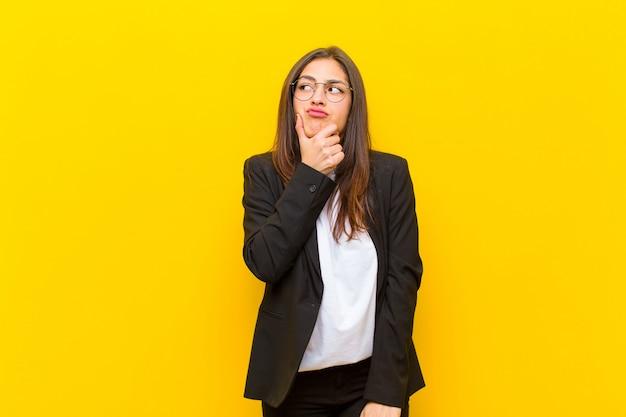 オレンジ色の壁にどの決定を下すのか疑問に思う若い女性