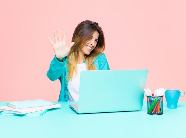 Молодая красивая женщина работает с ноутбуком, улыбаясь и глядя дружелюбно, показывая номер пять или пятый рукой вперед, считая вниз